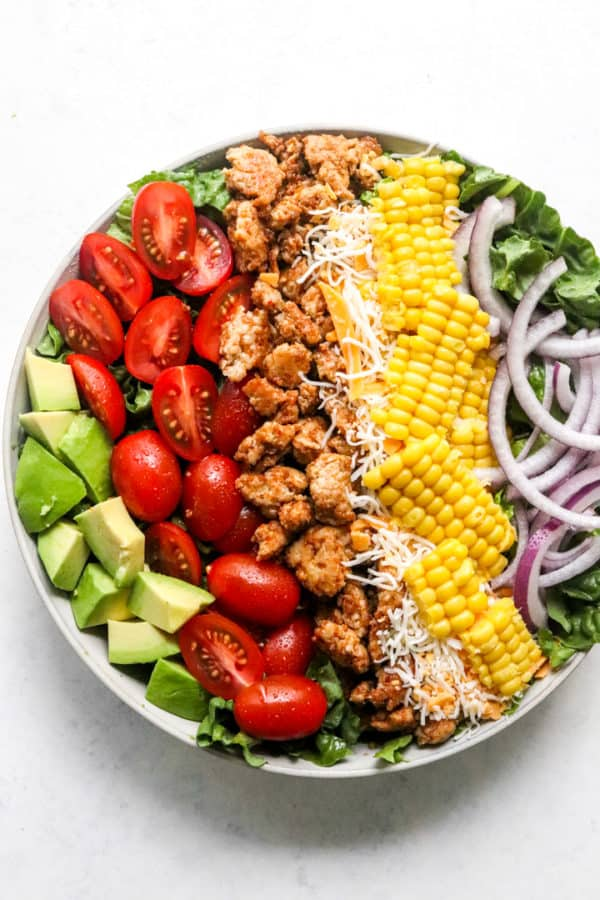 Diced avocado, sliced red tomatoes, cooked chicken, shredded cheese, corn, sliced red onion all piled on top of green lettuce in a round bowl