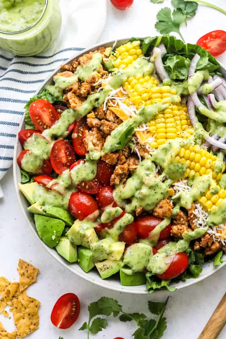 Large bowl of chicken taco salad topped with green creamy dressing with tortilla chips broken up next to it and a striped towel behind it