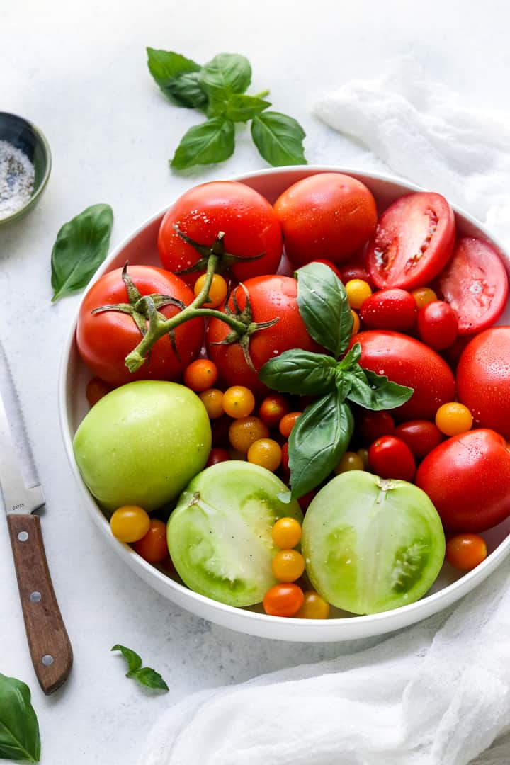 Large white bowl filled with red and green tomatoes with a knife next to it