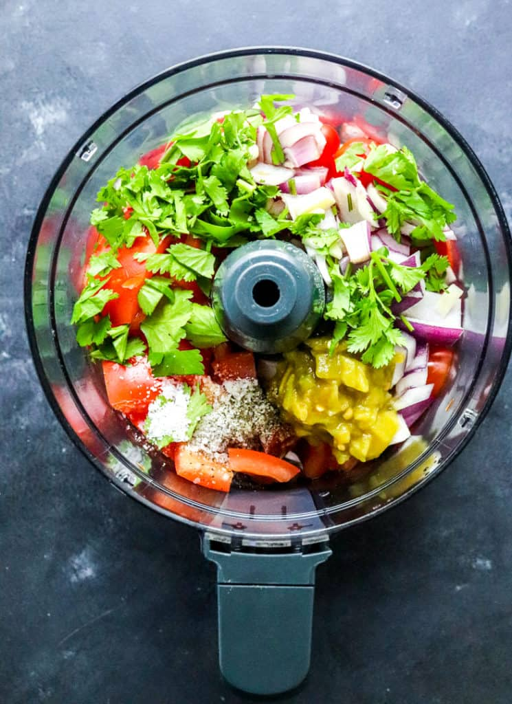 Tomatoes, chopped onion, herbs and chilies in a food processor