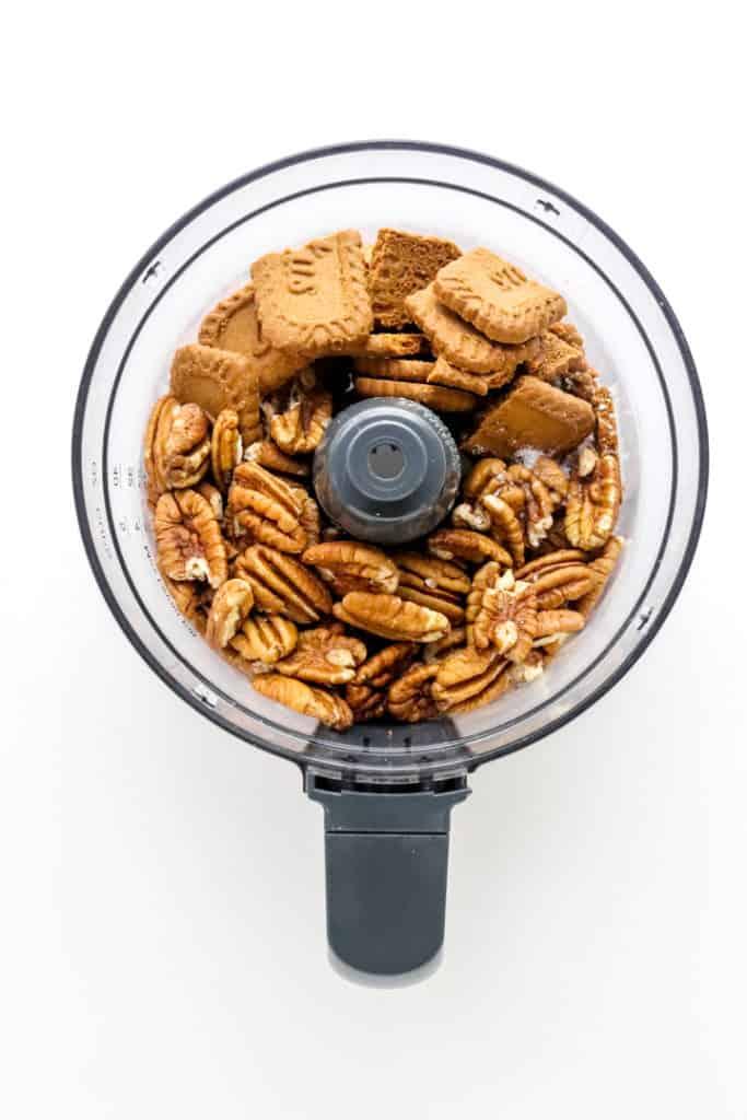 Food processor bowl with broken cookies and pecans in it