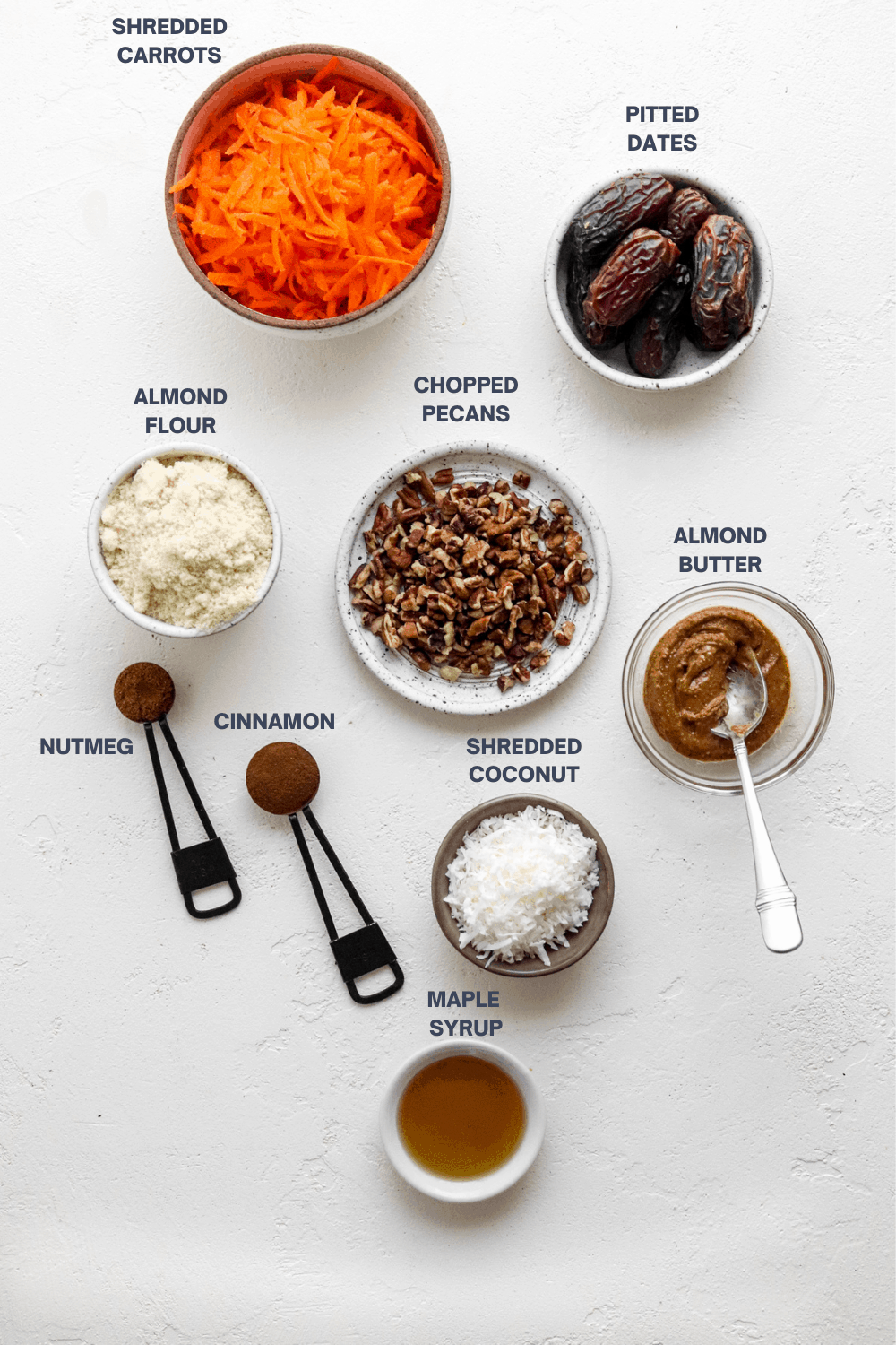 shredded carrots in a round bowl, whole dates in a round bowl. almond flour in a bowl, chopped pecans on a plate with almond butter in a bowl next to it.