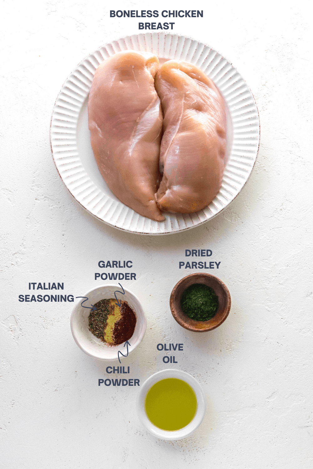 raw chicken breasts on a round plate with a brown bowl filled with green parsley in front of it and another bowl of spices next to it with a white bowl of olive oil in front of it.