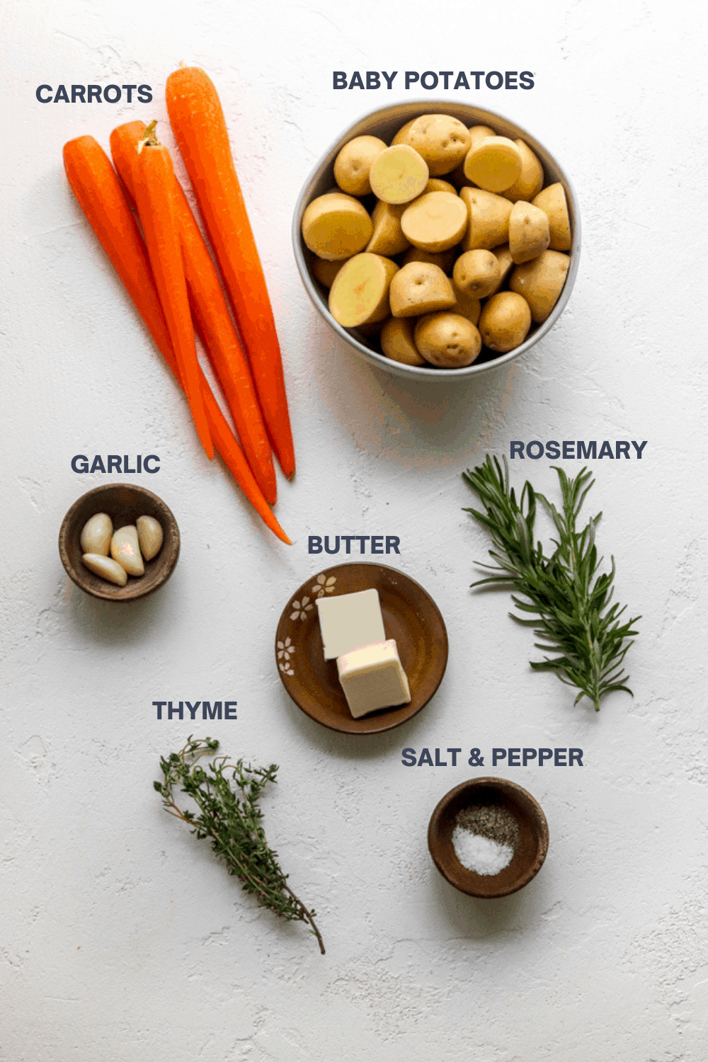 4 whole carrots next to a bowl of sliced potatoes, rosemary, thyme. garlic in a bowl, butter on a brown plate and salt and pepper next to it on a white surface.