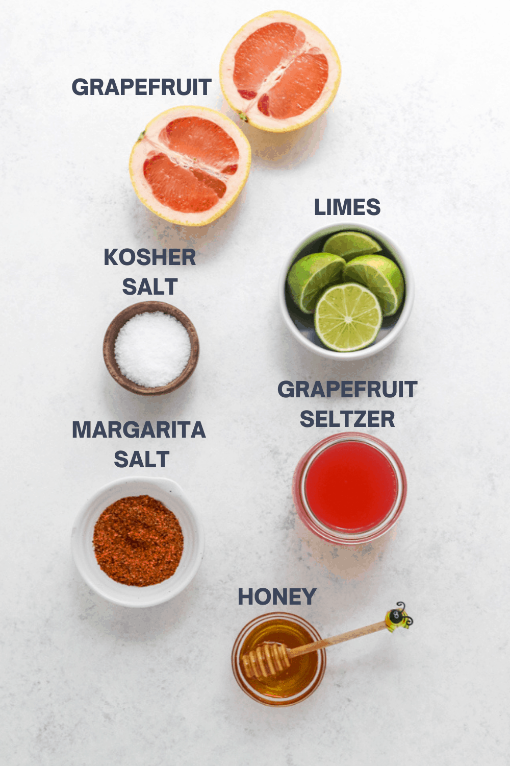 Sliced grapefruit, bowl of sliced limes, bowl of salt, pink seltzer in a glass and a bowl of red salt laid out on a white surface.