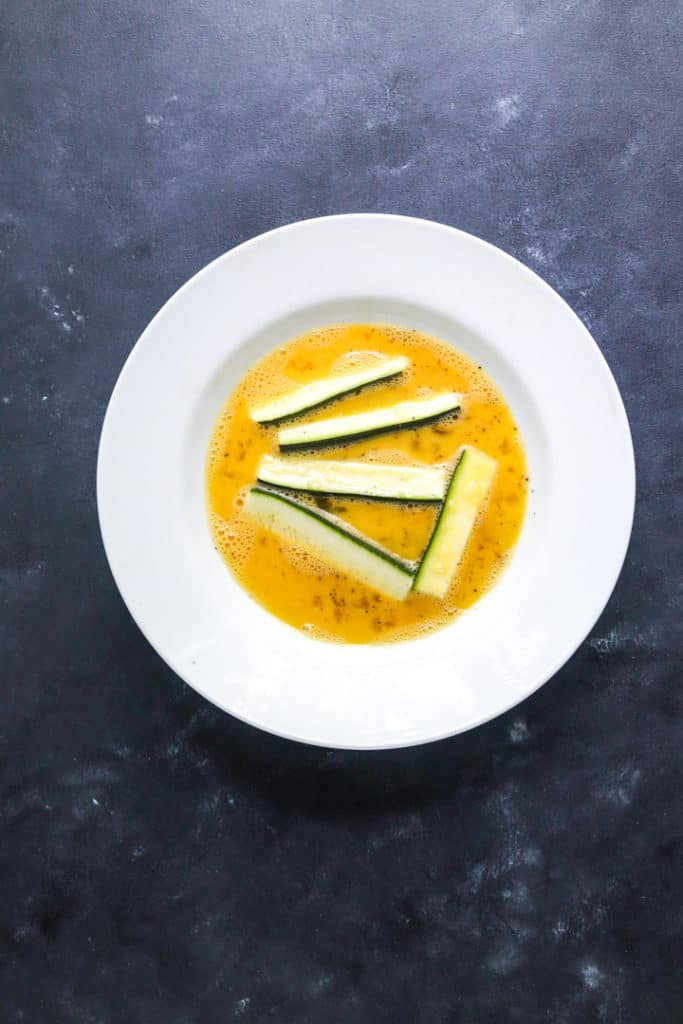 round white bowl filled with whisked egg and cut zucchini in it
