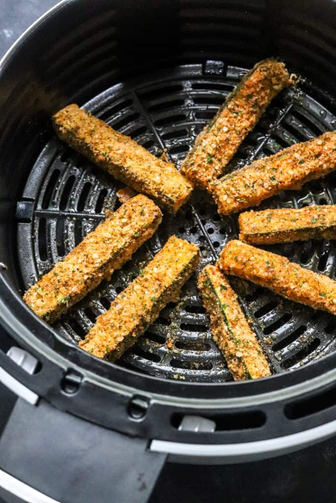 coated zucchini fries in an air fryer basket