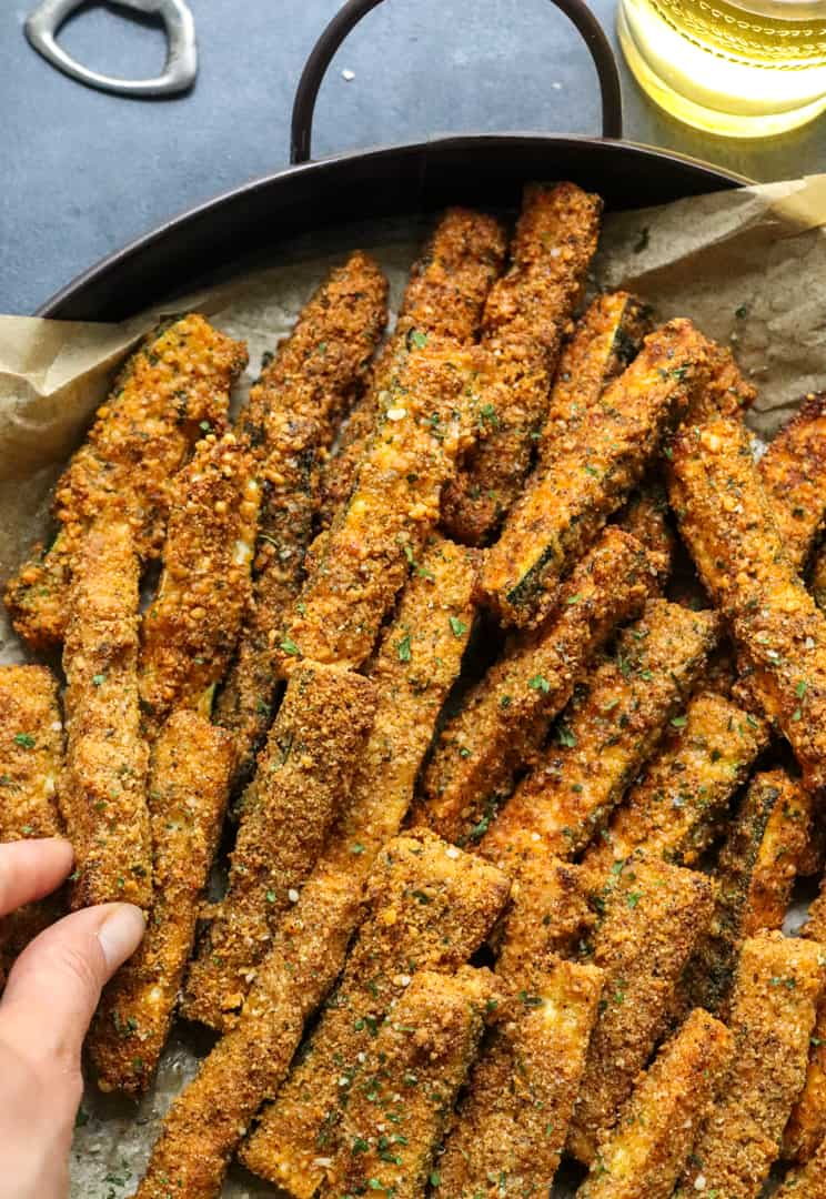 Hand grabbing a crispy zucchini fry from a large round platter of fries.