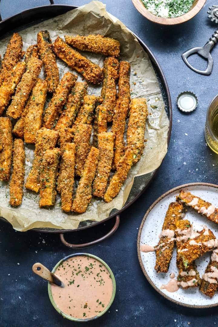 Metal tray filled with crispy zucchini fries on top of brown parchment paper with a bowl of orange sauce in front of it and a plate of fries next to it.