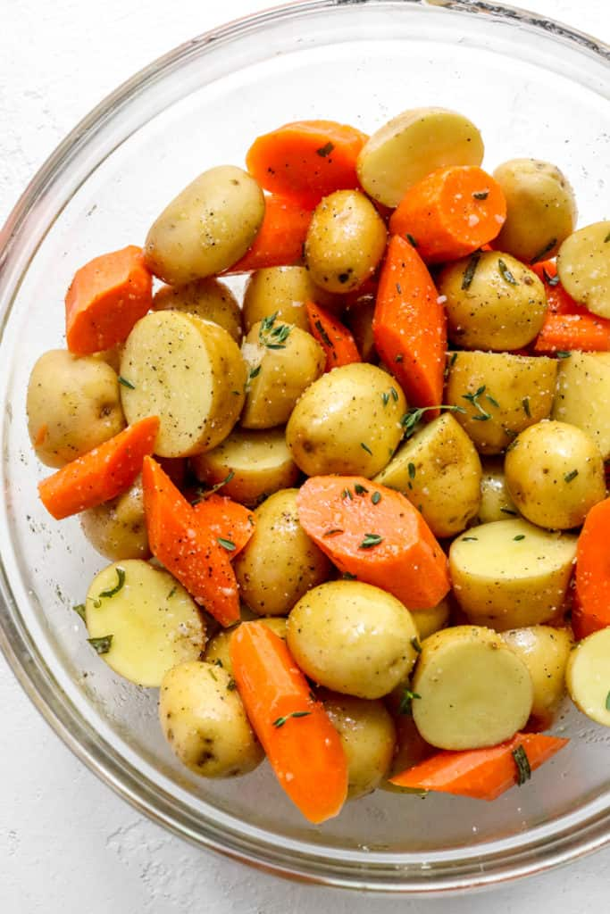 Here seasoned chopped carrots and potatoes in a round glass mixing bowl