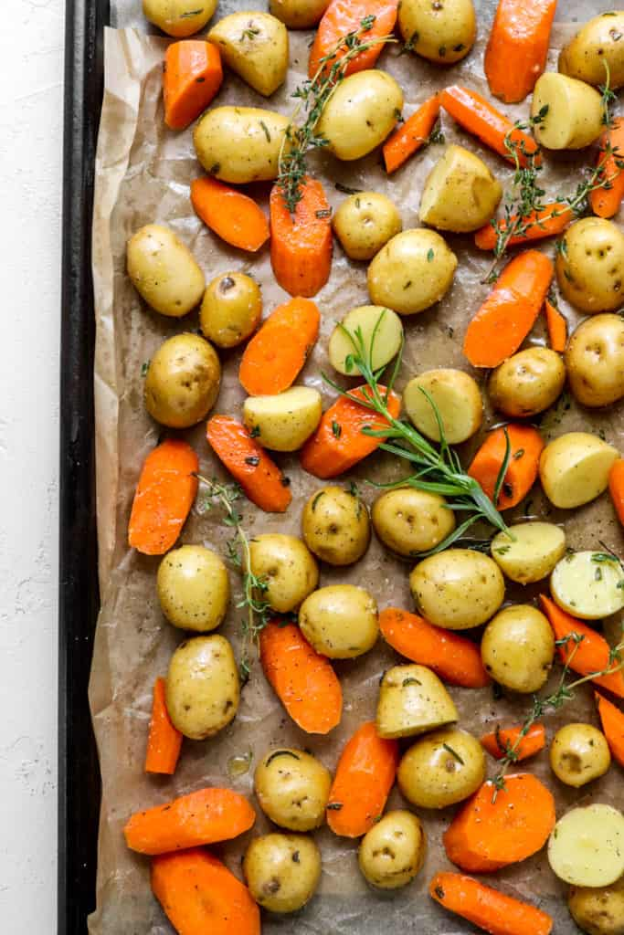 raw seasoned potatoes and sliced carrots on brown parchment paper with a whole piece of rosemary on top of it