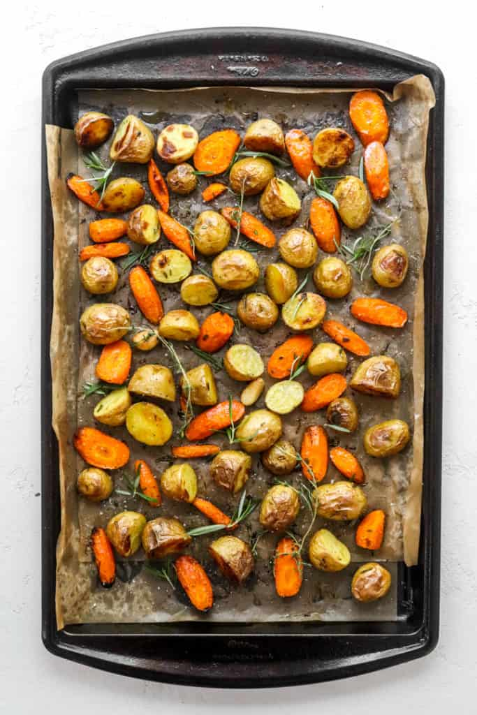Sheet pan topped with brown paper with crispy roasted potatoes and carrots on top of it