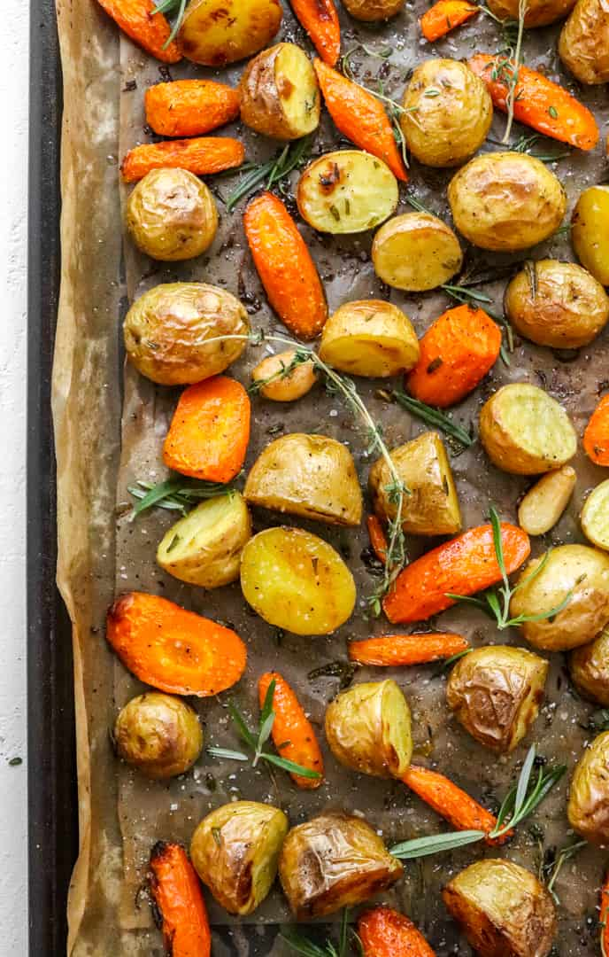 Oven roasted potatoes and carrots on brown parchment paper on a baking sheet with herbs on top of the veggies.