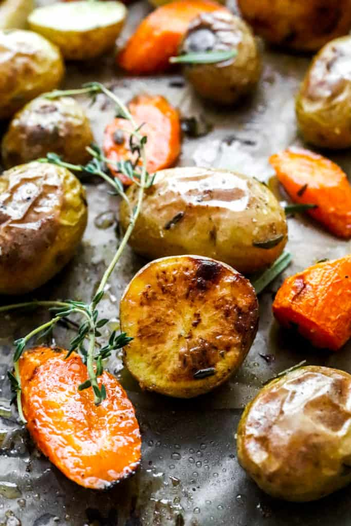 Close up shot of half of a crispy potatoes with more carrots and potatoes around it