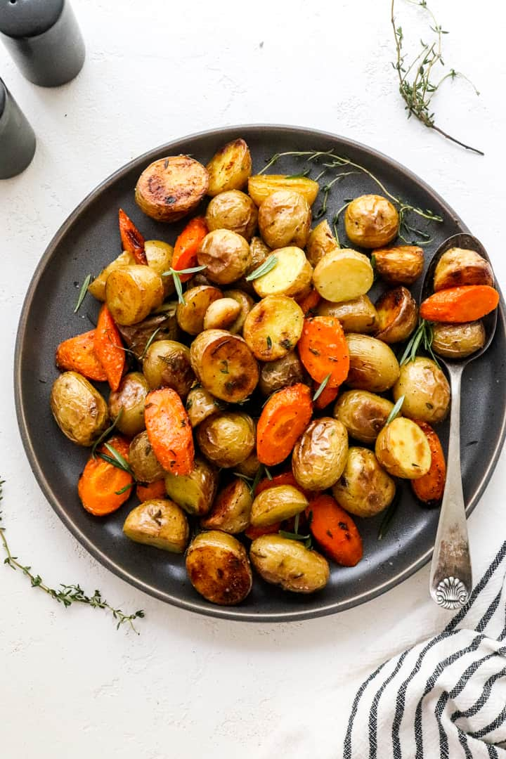 round grey plate filled with rotated veggies with a spoon on it on a white surface with thyme next to the plate.