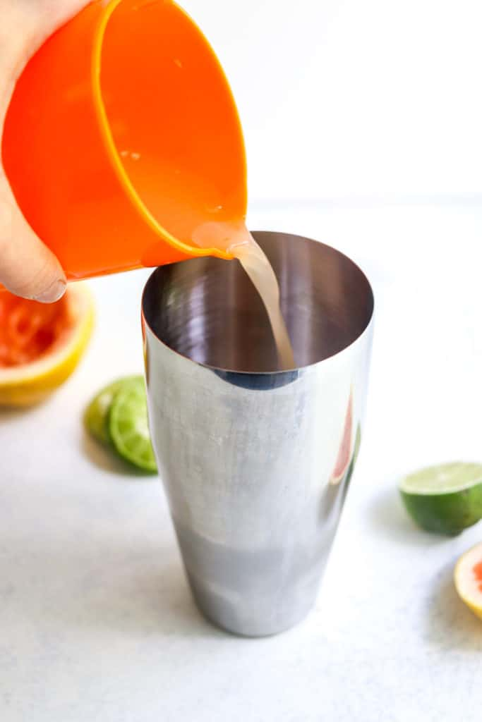 A hand pouring pink juice from an orange cup into a metal cup