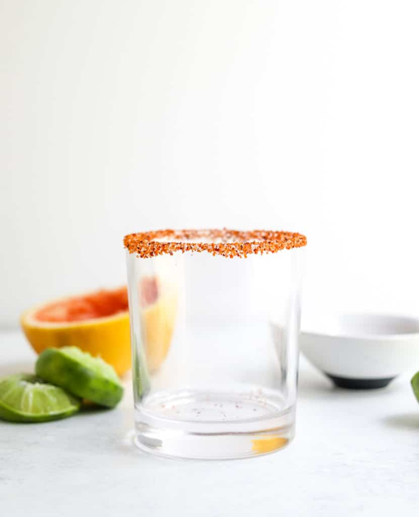 An empty short glass with seasoned salt on the rim with limes an a sliced grapefruit behind it
