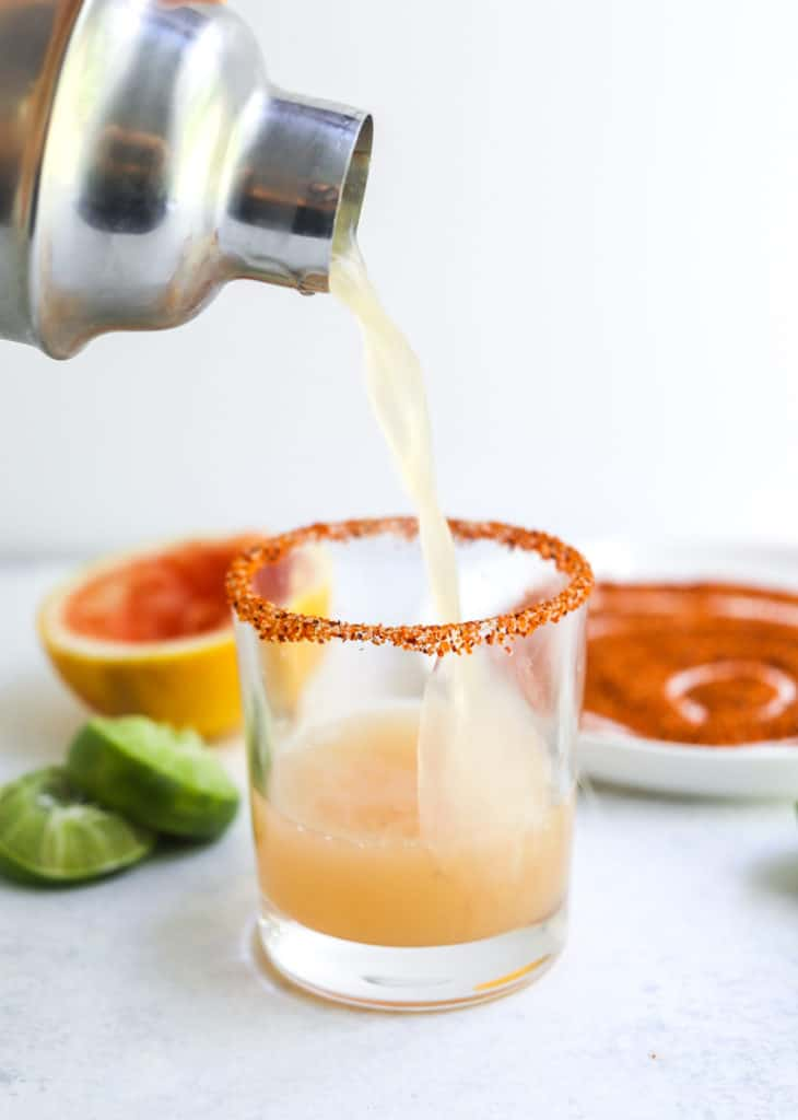 Metal pitcher pouring juice into a rimmed glass with cut limes and a plate of seasoned salt behind it