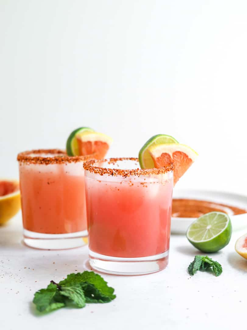 two glasses filled with grapefruit margarita with a lime and grapefruit wedge on the edge of the glasses and a dark salt rim with a sliced lime and mint leaves next to the glasses.