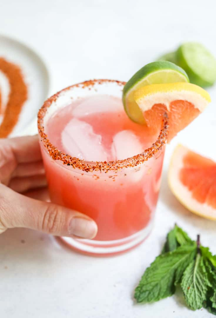 Hand holding a pink fruit margarita with a lime and grapefruit wedge on the side of the glass with sliced grapefruit behind it.
