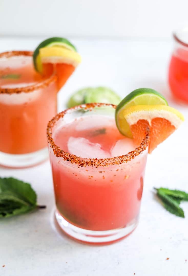 Small glass with a round rim detailed with seasoned salt and filled with pink liquid with slices of citrus on the glass with mint leaves around it and another drink behind it.