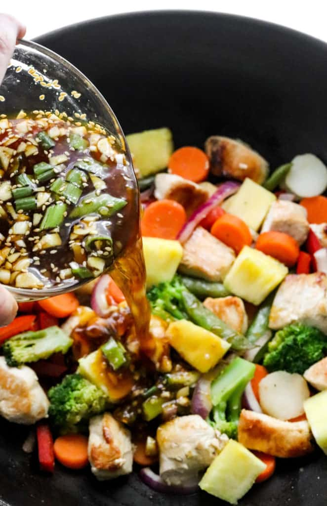 pouring teriyaki sauce over chicken and veggies in a pan