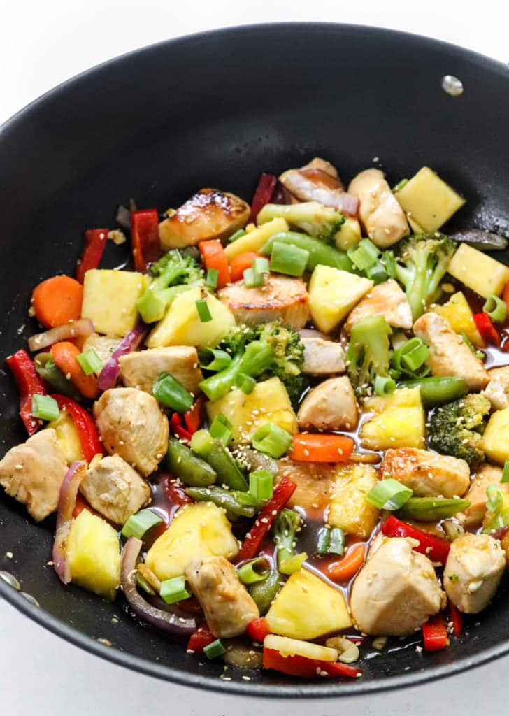 Chopped chicken, veggies and pineapple covered in a wet brown sauce in a round black pan