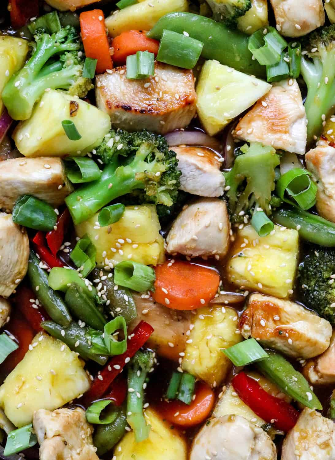 Close up shot of juicy cubed chicken, veggies and pineapple covered in teriyaki sauce with sesame seeds sprinkled on top of it.