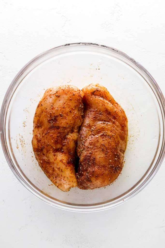 Two pieces of chicken breast covered in a spice rub inside a round glass bowl