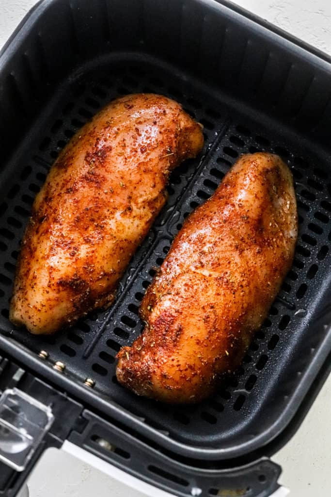 2 chicken breast, covered in seasoning inside of an air fryer basket