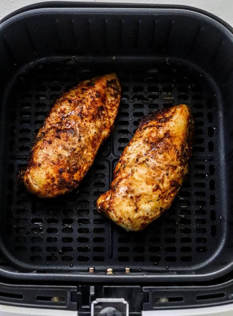 Cooked crispy boneless chicken breast in an air fryer basket