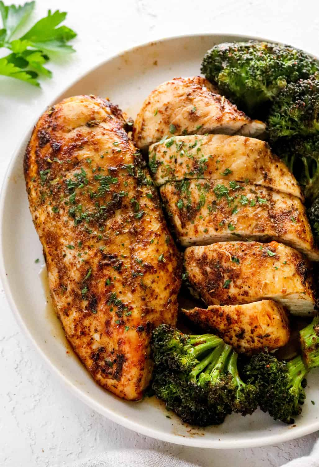 Close up of juicy chicken breast with seasoning on it and roasted broccoli around it on a round white plate on top of a white textured surface