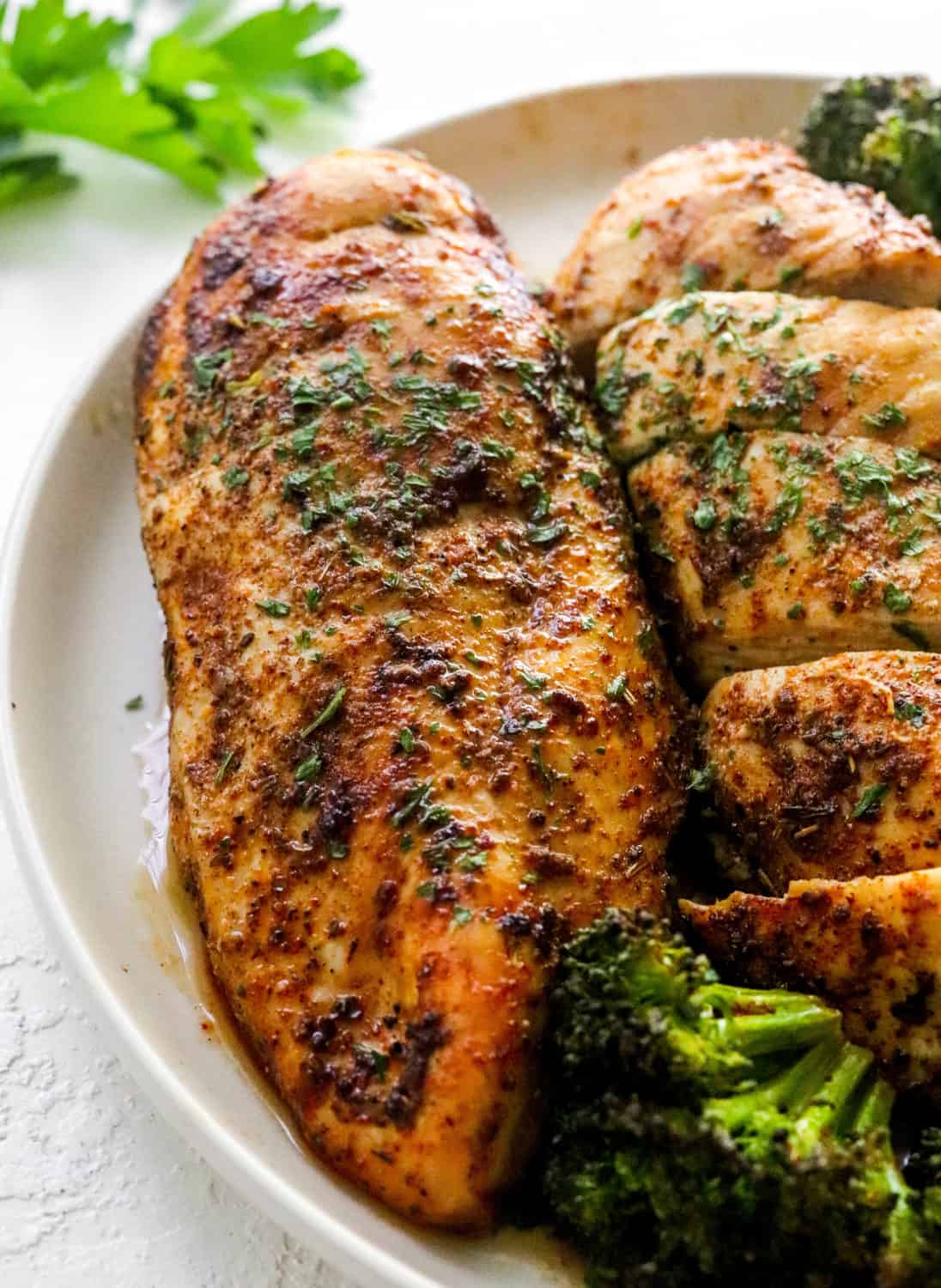 Large piece of crispy seasoned chicken breast on a round white plate next to another piece cooked chicken that is sliced, with some cooked broccoli next to it.