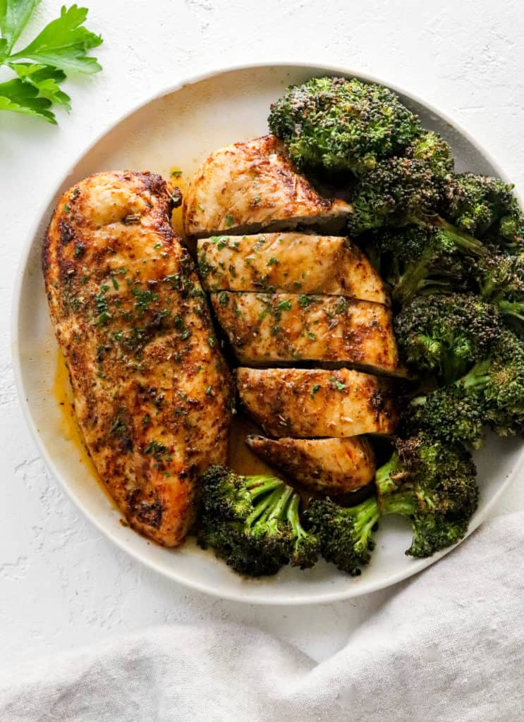 Seasoned cooked chicken beast on a round white plate with another pieces of sliced chicken next to it and cooked broccoli around it on the plate