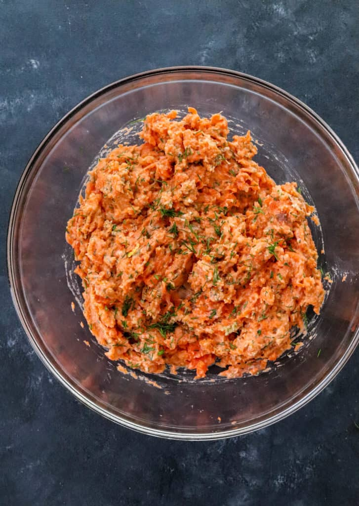 salmon burger mixture in a round glass bowl on a dark blue surface