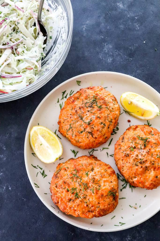 3 cooked salmon patties on a round plate with dill on them and lemon wedges on the plate with a bowl of creamy Cole slaw behind it