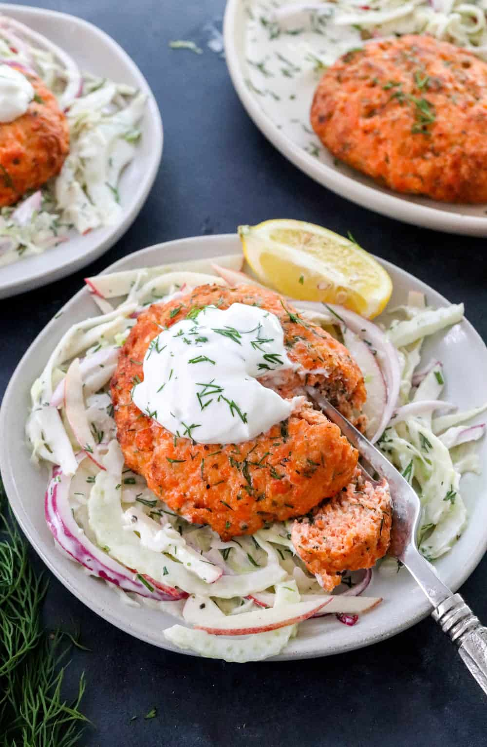 3 plate of Cole slaw with cooked round salmon patties onto of the slaw and a fork cutting through one of them