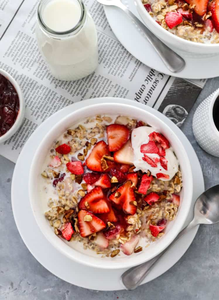 White round bowl on top of a plate filled with creamy oatmeal with glazed chopped strawberries on top of it with a bowl of jam and a cup of coffee next to it