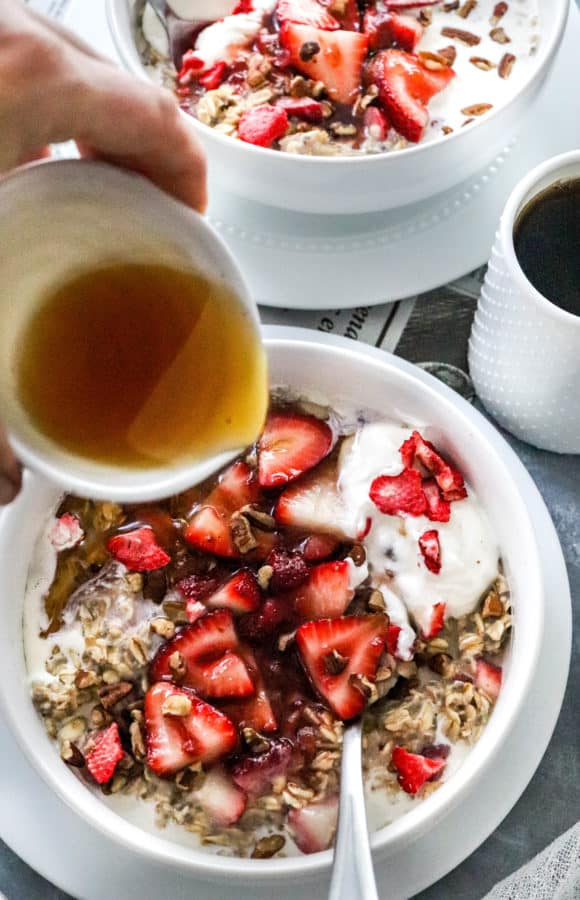 Maple syrup being poured into a bowl if oats and strawberries with a white cup of coffee next to it