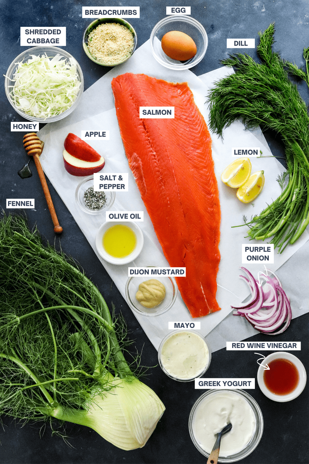 large piece of fresh salmon with dill, fennel bulb, cabbage, red onion around it with bowls filled with Greek yogurt, mustard, mayo, vinegar, salt and pepper near it.