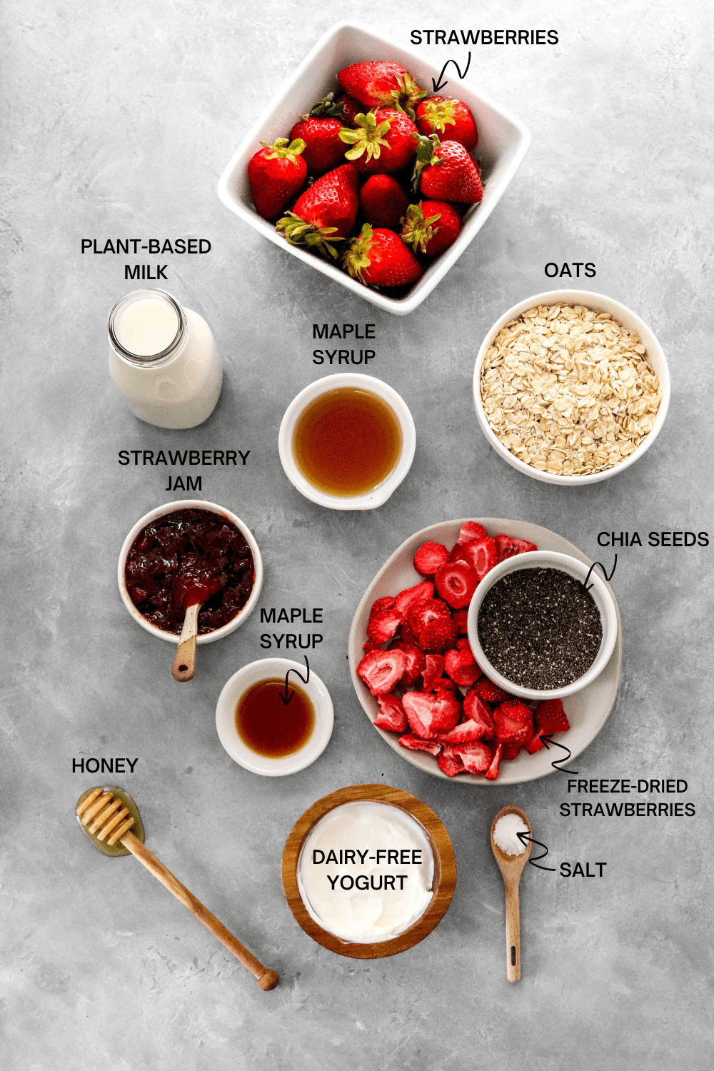 Square white dish filled with strawberries with a bowl of oats, glass of milk, maple syrup, bowl of jam, plate of dried fruits and chis seeds and a bowl of Greek yogurt in front of it on a gray surface.