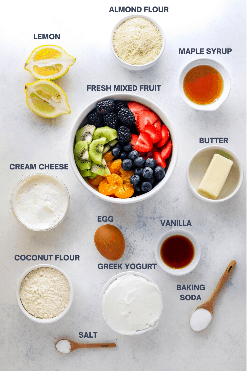 Small white bowl filled with almond flour with a sliced lemon, bowl of mixed fruit, bowl of maple syrup, cream cheese, butter, egg, vanilla, yogurt in bowls in front of it with two wooden measuring spoons in front of it filled with baking soda and salt on a white surface.