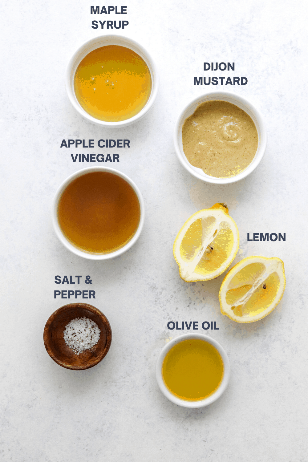 Small white bowls filled with mustard, vinegar and honey spread out on a white surface with a sliced lemon next to one of the bowl and a wooden bowl filled with salt and pepper in front of it.