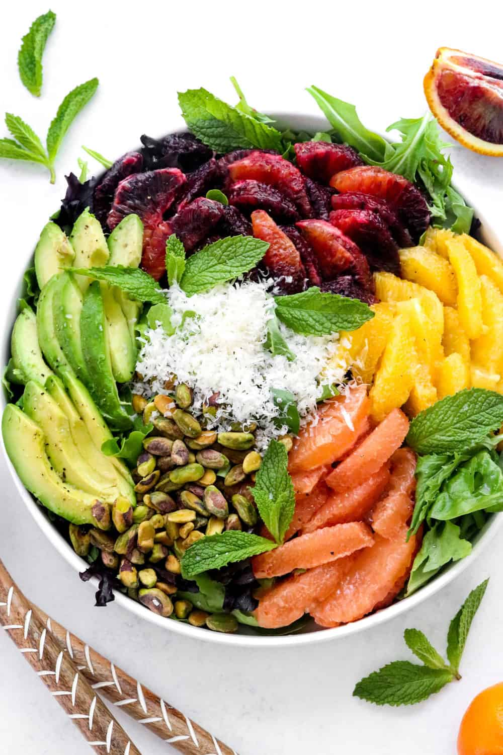 round plater filling with mixed greens topped with segmented oranges and grapefruit, sliced avocado, shredded cheese and pistachios.