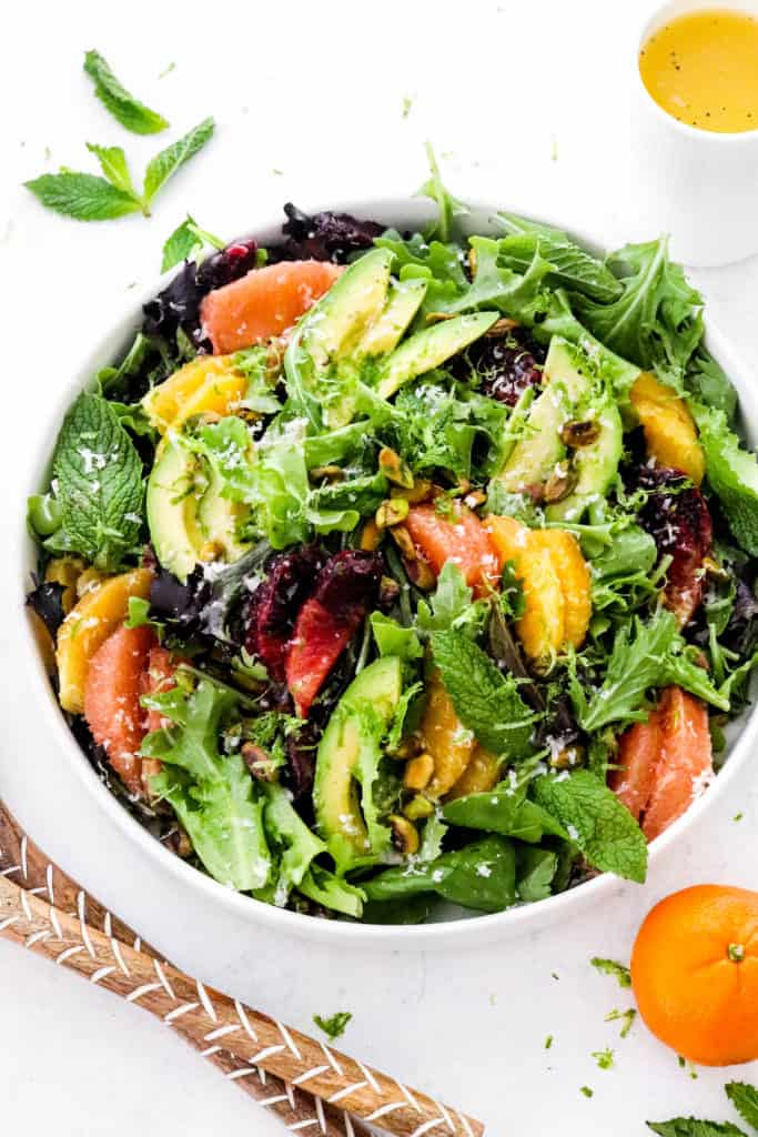 Round white platter filled with greens mixed in with sliced grapefruit, oranges, avocado, nuts and mint