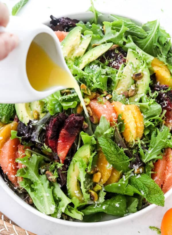 pouring dressing onto a mixed citrus salad