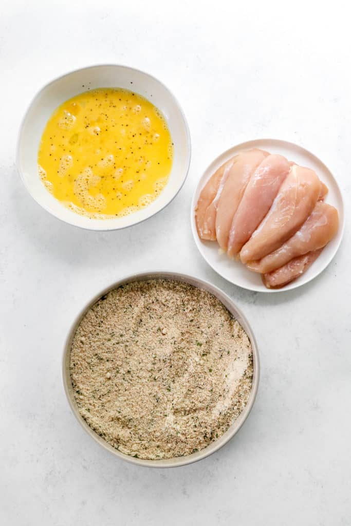 Bowl of whisked eggs next to a bowl of breading with raw chicken in it with a plate of sliced raw chicken behind it.