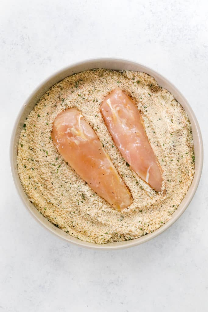2 raw chicken tenders in a bowl filled with almond flour and spices