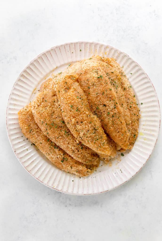 Round white textured plate with a pile of raw breaded chicken on it