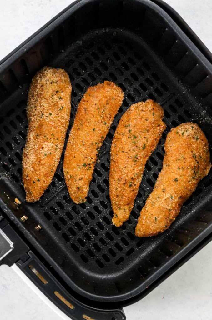 Coated chicken tenders in an air fryer basket